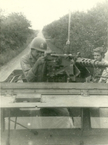 HB Stevens Jr behind 50 cal. anti-tank gun. Radio areal and equipment behind him. Sgt Coulter on seat